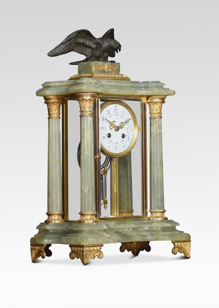 Late 19th century French onyx clock set, the case surmounted with a cast bronze eagle upon a rectangular plinth, supported on four fluted Corinthian columns applied with gilt metal mounts, encasing the four glass panels encasing the enameled dial