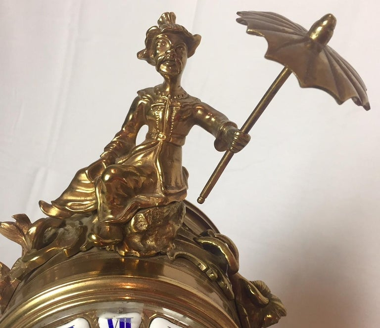 This exquisite French ormolu and bronze clock of a chinoiserie figure holding an umbrella and sitting astride an elephant typifies the fascination of 18th century France with all things oriental. The circular clock dial is bordered with a foliate
