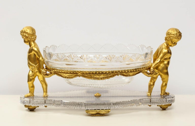 A French ormolu or bronze and cut-glass centerpiece by Baccarat Paris, circa 1870.  The center bowl supported on basket, flanked by two cherubs resting on ormolu supports, shaped cut-glass basket.  Very good condition. Ready to place.  Measures: