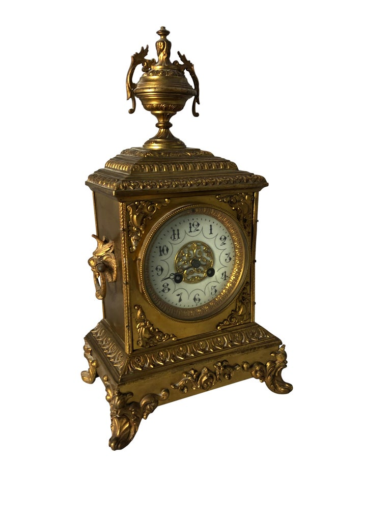 A fine quality French Ormolu mantel clock, 19th century, in Sevres Manner. The ornate case with finely cast detailed mouldings and cornice, surmounted by a floral decorated urn, the front set with porcelain plaque, raised on floral feet, the dial