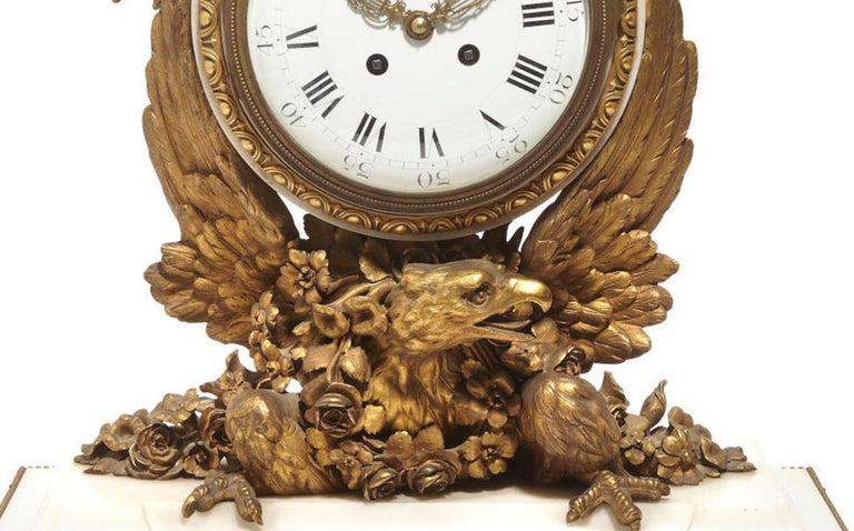 Spectacular and unique French Napoleon III ormolu mounted white marble mantel clock, 19th century.  The clock is surmounted by a gilt bronze pineapple finial with ribbons over a porcelain clock face with Roman Numerals enclosed into an ormolu egg