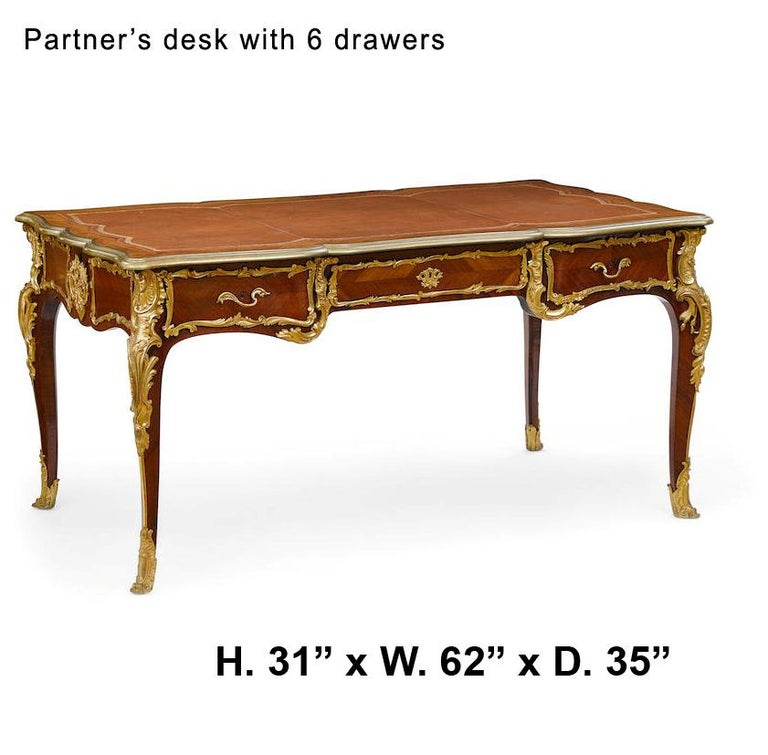 Spectacular and unique 19th century French Louis XV style ormolu-mounted Kingwood partner's desk. The shaped top is with an inset tooled leather writing surface and an ormolu border, over a veneered kingwood frieze fitted with three drawers to each