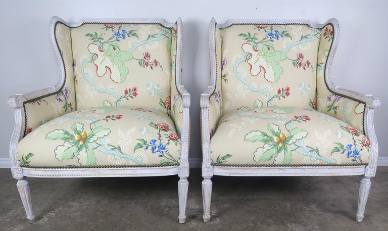 Pair of early 20th century French painted wingback armchairs standing on four straight fluted legs. The armchairs are painted in a French gray that is worn throughout exposing the wood underneath. The chairs are newly upholstered in a vintage (but