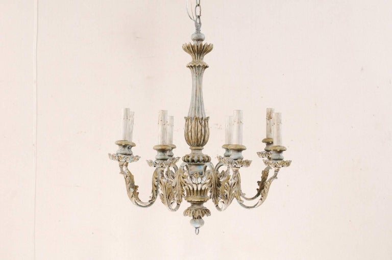 A French eight-light painted wooden chandelier from the mid-20th century. This French chandelier has carved central column with wrapped leaf carvings and fluting details, bottom ring finial, and lovely scrolled metal arms that are decorated with