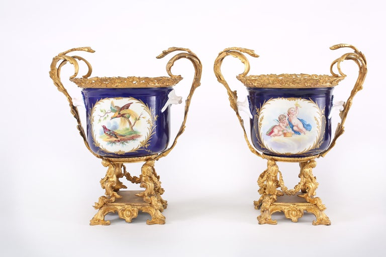 French pair Sèvres-style gilt bronze mounted porcelain decorative vases / Urns with exterior painted design details. Each vase / urn is in good condition. Minor wear consistent with age / use. Maker's mark undersigned. Each piece stands about 15-1/2