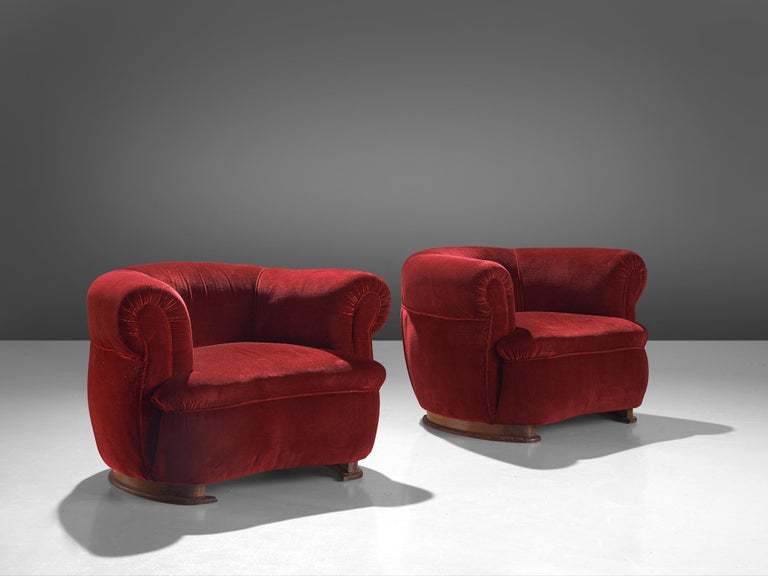 Pair of lounge chairs, oak and red velvet, France, 1940s.  Wide and comfortable chair in red fabric upholstery. Truly extraordinary theatrical lounge chairs that feature a very rounded seat and curved armrests. The seat is thick and widens