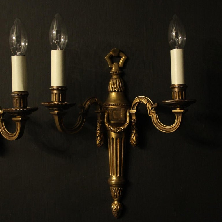 A French pair of gilded bronze twin branch antique wall lights, the leaf clad reeded scrolling arms with circular bobeche drip pans and millgrain reeded candle sconces, issuing from a laurel swaged foliate reeded tapering back plate, with pierced