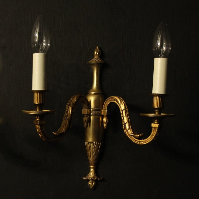 A French pair of gilded bronze twin branch antique wall lights, the leaf clad square gauge scrolling arms with circular bobeche drip pans and reeded candle sconces, issuing from a bulbous tapering leaf back plate, nice color and scale. Fully rewired
