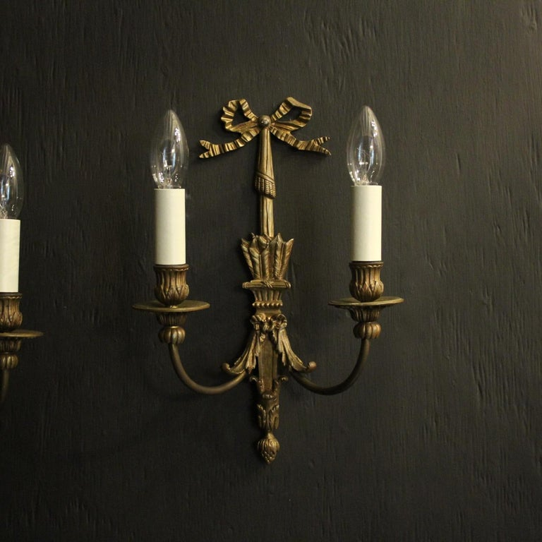 A French pair of gilded bronze twin arm antique wall lights, the scrolling arms with leaf bobeche drip pans and reeded candle sconces, issuing from an ornate tapering arrow sheath back plate with pierced ribbon finial, nice proportions with good