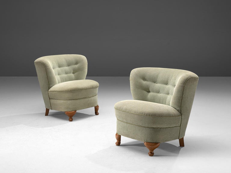 Pair of lounge chairs, fabric and wood, France, 1950s  These elegant, curved chairs are bold and round. The backrest flows slightly outwards when seen from the seat which is the reason that this chair has a very dynamic look. This voluptuous chair
