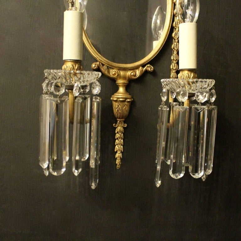 A French pair of gilded cast bronze twin arm antique girandoles, the reeded scrolling arms with glass bobeche drip pans and bulbous leaf candle sconces, issuing from an ornately cast oval mirrored backplate with central floral basket final and