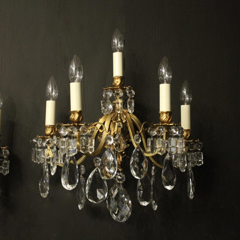 A French pair of gilded bronze and crystal five arm double tiered antique wall lights, the reeded scrolling arms with leaf bobeche drip pans and bulbous leaf candle sconces, issuing from a foliated cartouche backplate and decorated overall with