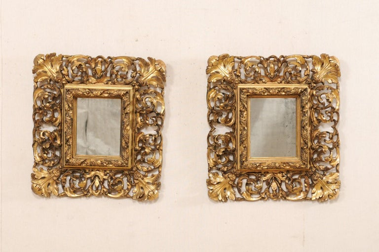 A pair of French ornately hand carved and giltwood mirrors from the early 19th century. This pair of antique Rocaille, style mirrors from France each feature a richly pierced-carved rinceaux décor surround with curling acanthus leaves, and inner