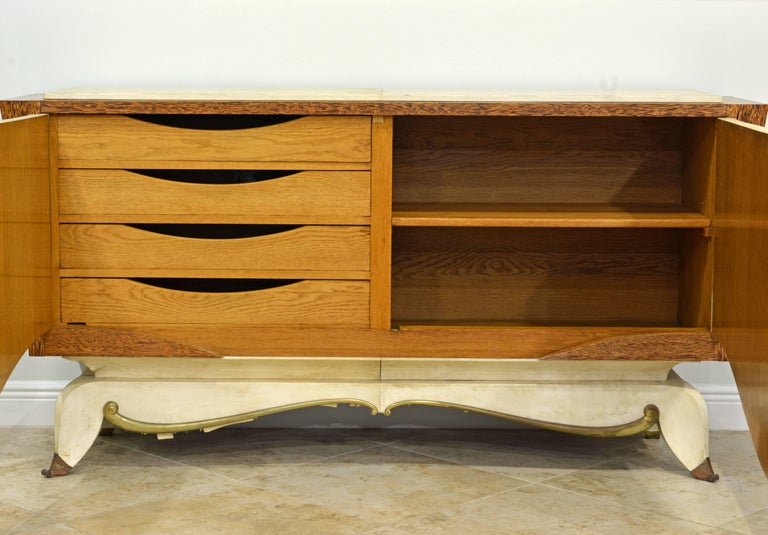 This sculptural piece of French Art Deco furniture features a combination of parchment clad surfaces and wonderful Macassar wood accented by a scrolled bronze trim and bronze sabots. Very unique and elegant. The two-shaped and curbed doors open up