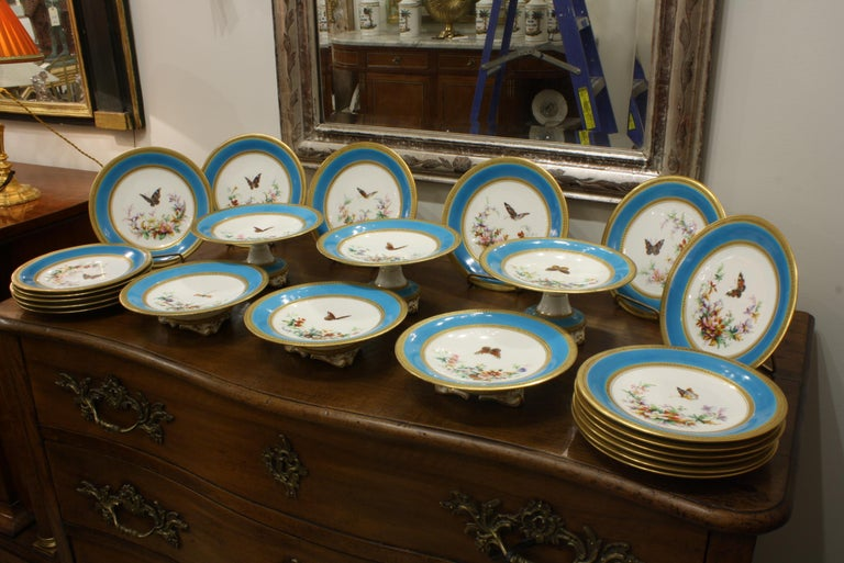 Extraordinary porcelain dessert service attributed to Minton comprising 23 pieces with turquoise ground, hand painted butterflies, flowers and floral garlands. The perimeters and inside diameters of the plates are beaded and gilded. The service
