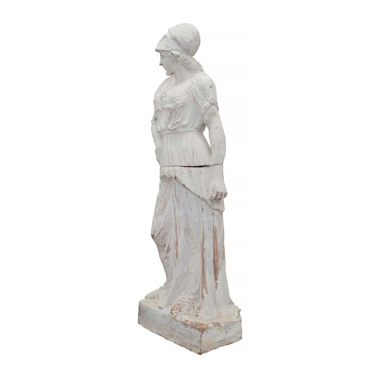 A beautiful large scale French 19th century patinated terracotta statue of a maiden. The two-piece statue is raised by a rectangular base where the maiden stands. She wears sandals and is draped in period attire. Through her attire, her armor can be
