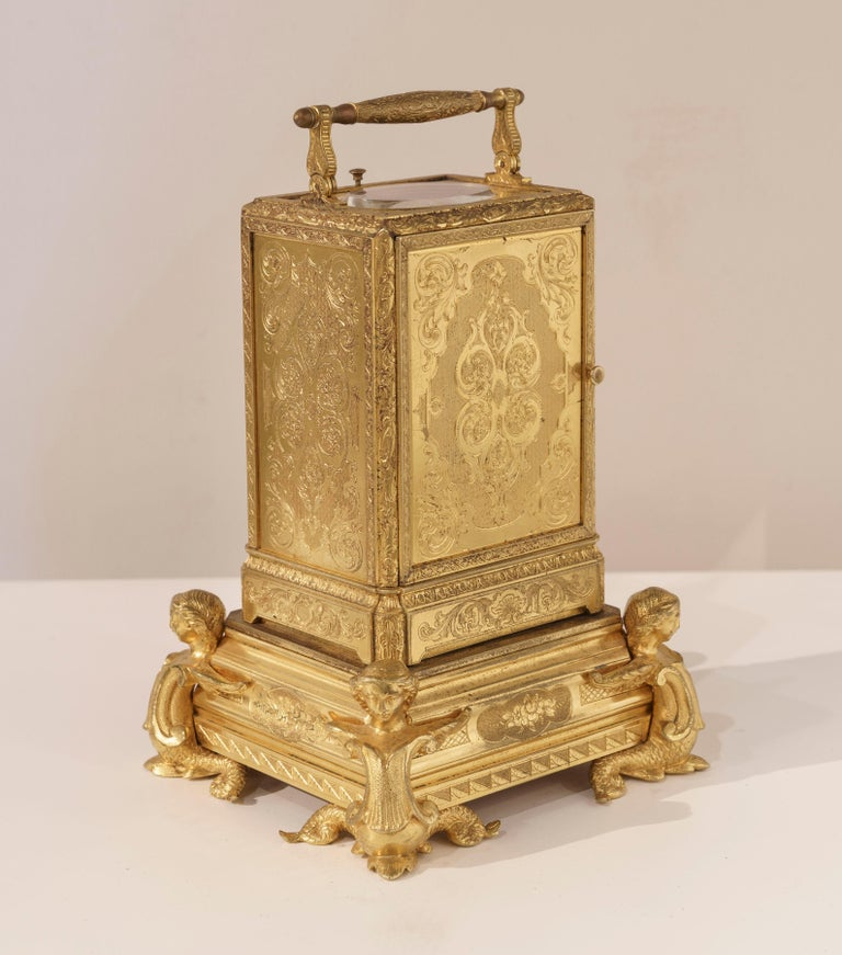 A Petit Sonnerie carriage clock by Grohe of Paris  The gilt bronze case comprehensively engraved, and having a retractable carrying handle; the lever movement driving the petit sonnerie movement, with the fascia indicating, on white enamel faces,
