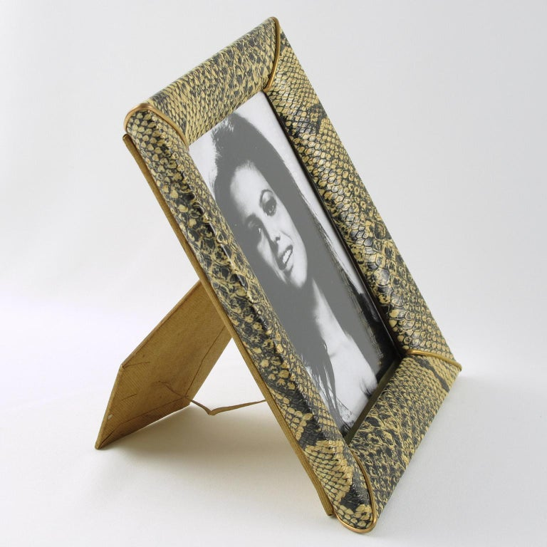Lovely 1960s modern French picture photo frame. Decorative imitation leather or vinyl with faux python snakeskin textured pattern and brass accents. Easel at the back. The frame can be placed in a portrait or in landscape position.