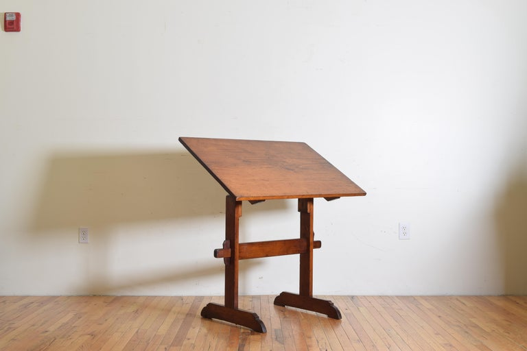 The adjustable rectangular top resting upon trestle-form legs and having iron notched dials for securing the top, joined by a vertical stretcher, raised on elongated bracket feet, height suitable for standing or setting on a stool.
