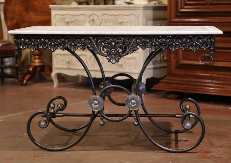 This large butcher table, or pastry table, would add the ideal amount of surface space to any kitchen. Crafted in France, this table stands on four scrolled legs over an intricate stretcher and decorative mounts and finials. The table has a