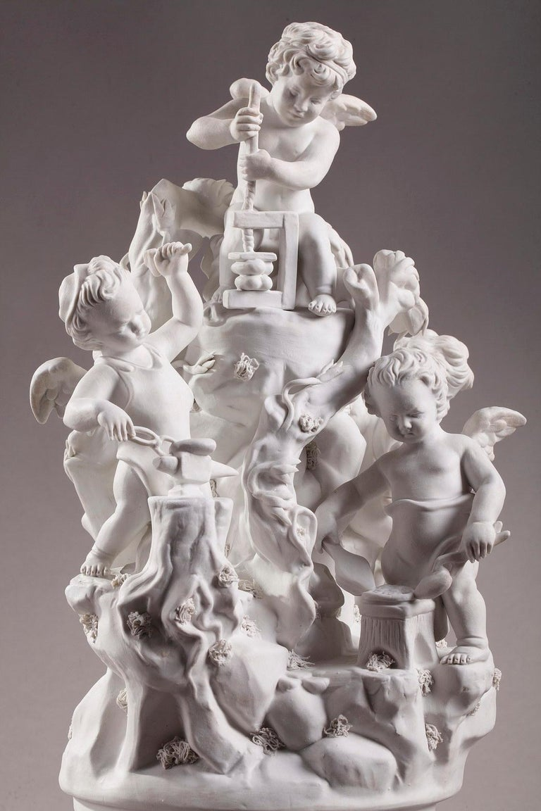 19th century Napoleon III French? Porcelain? biscuit group featuring four young Cupids working in the forge. They rest upon a white and blue? porcelain? base, embellished with intricate gilded foliage. After a model by Sèvres? porcelain?