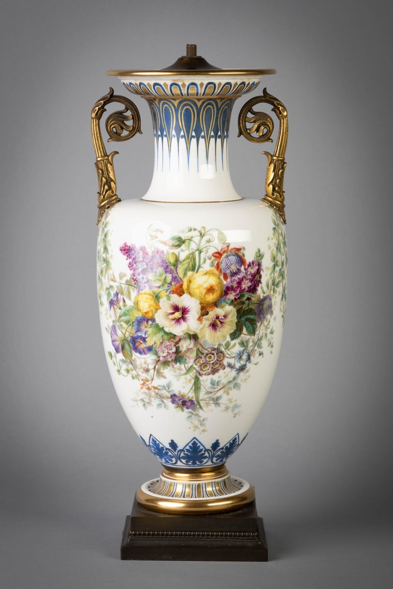 Of slender baluster form, painted with large sprays of mixed flowers hanging from vine garlands above a blue enamel lambrequin band at the base, the shoulder affixed with two gilt-bronze foliate scroll handles, with blue enamel and gilded formal