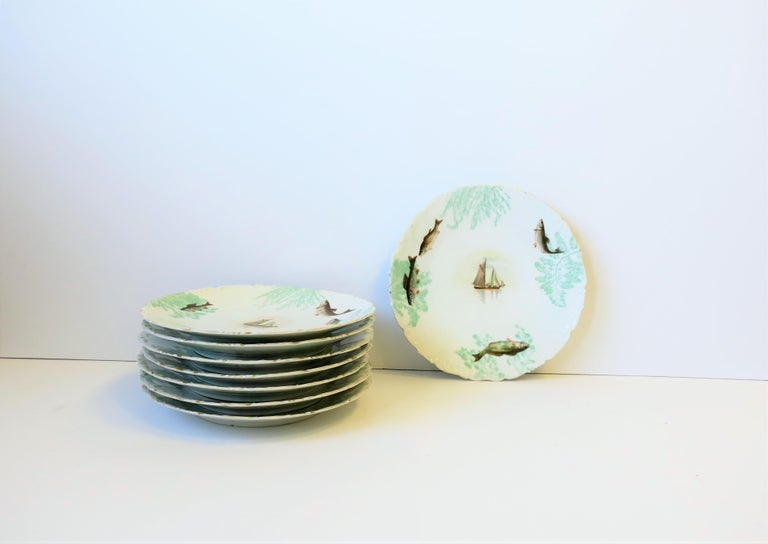A gorgeous set of 8 French T & V Limoges lunch or dinner plates in an Adirondack design, circa early-20th Century, France. There are 8 plates in set, with three varying design scenes. Scenes include fishing boat, beach, bass fish, and plant design,