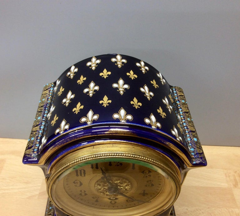 French Porcelain mantel clock standing on a raised plinth and resting on   Beautifully decorated break arch case with Fleur de lys on a midnight blue ground.  Brass bezel supporting the gilded dial with Roman numerals and original hands.