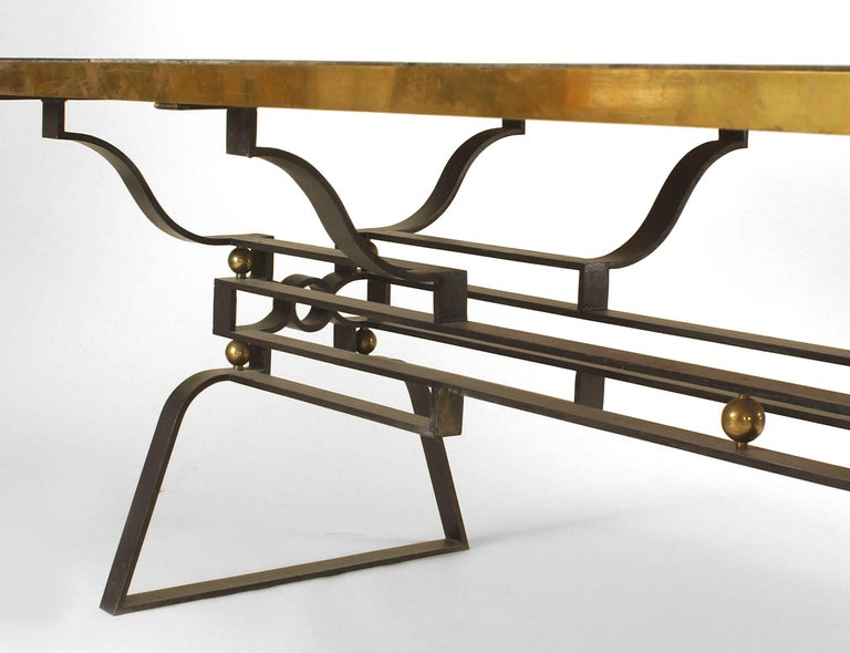 Attributed to Gilbert Poillerat, a French Post-War Design 1950s iron dining table with a geometric design stretcher and trimmed with bronze balls and top rim with a sectioned inset black marble. Mid-century.