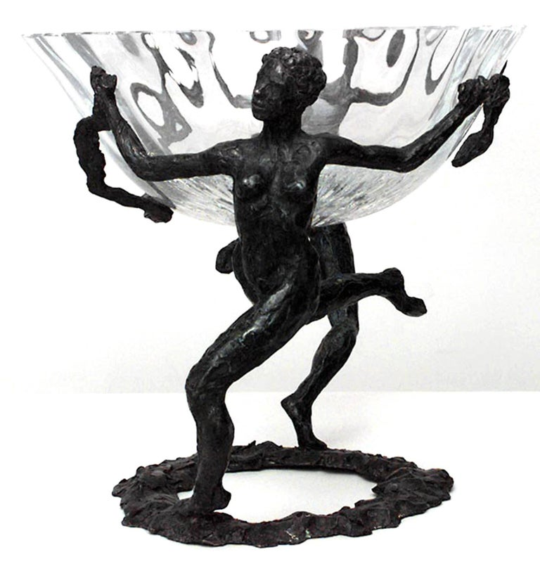 Signed by the French artist LaRoche, this Art Moderne centerpiece is composed of an elevated crystal bowl supported mid-air by two textured bronze figural handles that activate the space with their dynamic poses and sensual forms.
