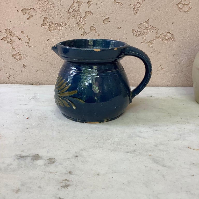 19th century blue ceramic pitcher with white flower from Savoie, France. No maker's mark. Minor wear.