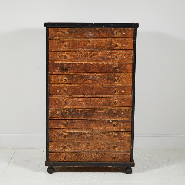 French Primitive tall chest of drawers, the body consists of a black painted frame with rustic wooden drawers. Each drawer is shallow and is the same size.