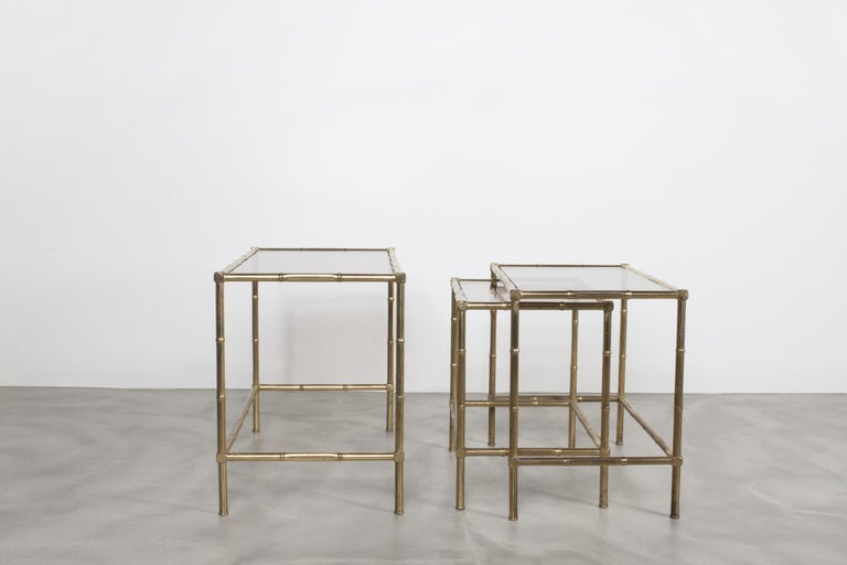 Set of three nesting tables in patinated brass metal with stylized hand-forged bamboo design.