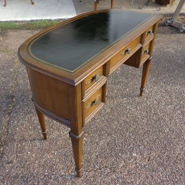 French Provencial writing desk by Sligh Furniture  Vintage leather top half moon desk by Sligh. Walnut and tooled black leather top. Five drawers with brass filigreed pulls and plates. Finished back.     Measures: Height: 29.5 inches Width: