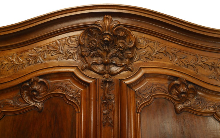 French Provincial 18th century walnut two door large scale armoire with foliate carved detail on doors and cornice with original hardware supported on a flat base.