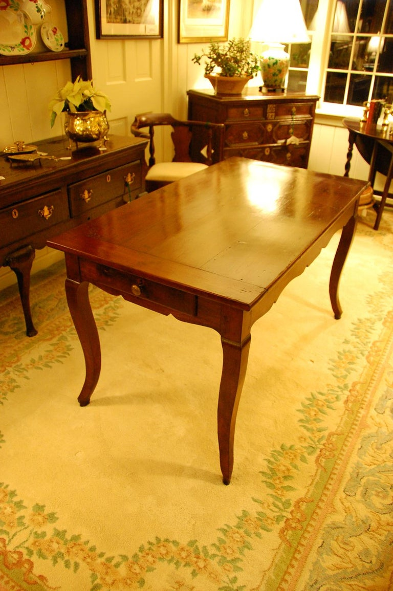 French Provincial mid-19th century small cherry farmhouse dining table with cabriole legs and gracefully shaped skirt. There are two drawers (one on each end of the table), a chopping board was removed sometime in the last 100 years and the legs