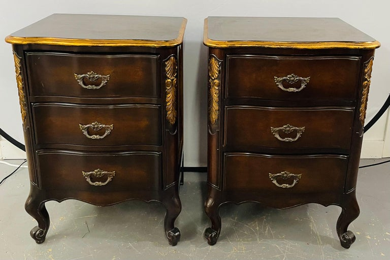 An early 20th century pair of French provincial / Country nightstands finely hand carved in solid Mahogany and showing a beautiful curve and acanthus design gilt decorated. Each nightstand features three drawers and original pulls. The timeless