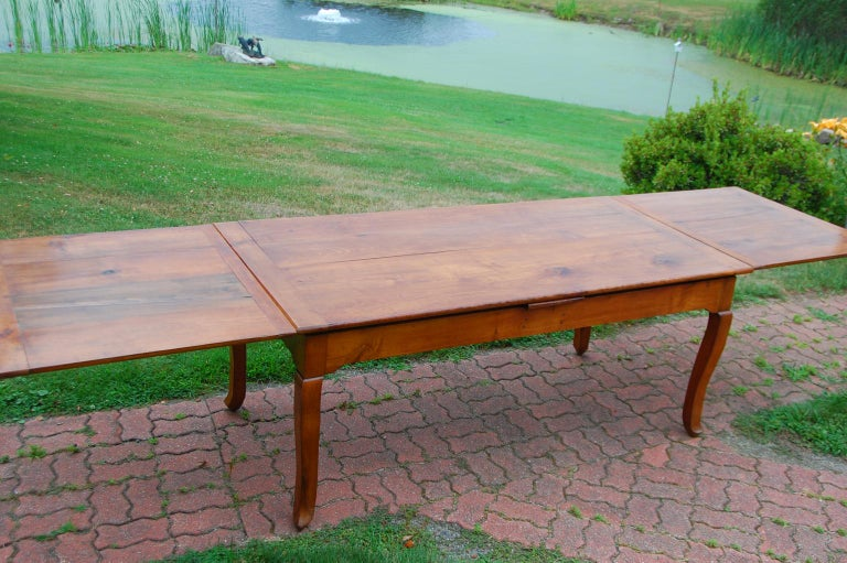 French provincial cherry farmhouse extending table with cabriole legs and two pull out leaves; pegged, mortise and Tenon construction. This table has been modified so it is level whether or not one or both leaves is extended. To do this we had to