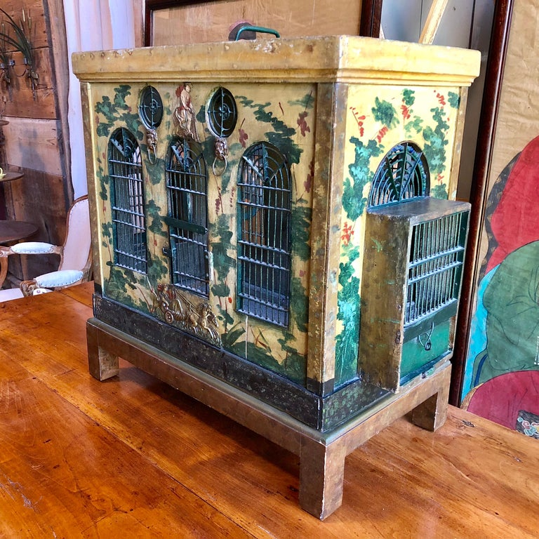 A charming Provincial French folk-art birdcage circa 1850 in wood and wire with painted brass decorative appliques, Palladian style wire windows, bird feeding trays, cobalt blue glass beads, cleaning tray and air vents. Painted with vines and