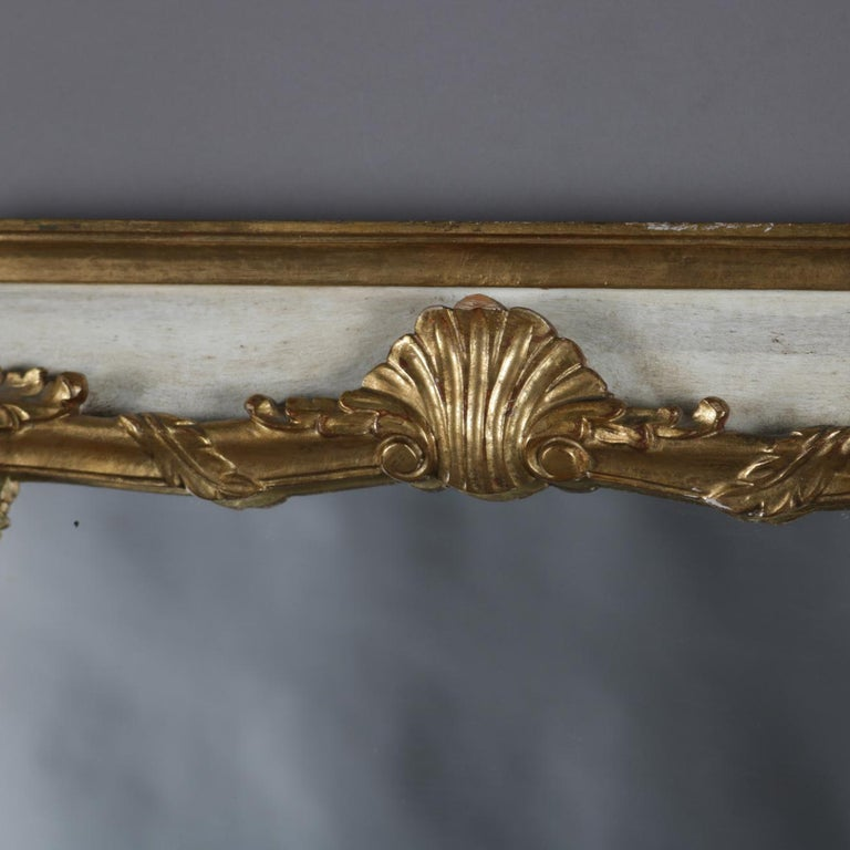 French Provincial wall mount dressing mirror features frame with whitewash painted ground and foliate and scroll form giltwood bordering having shell form crest, 20th century   Measures: overall 47