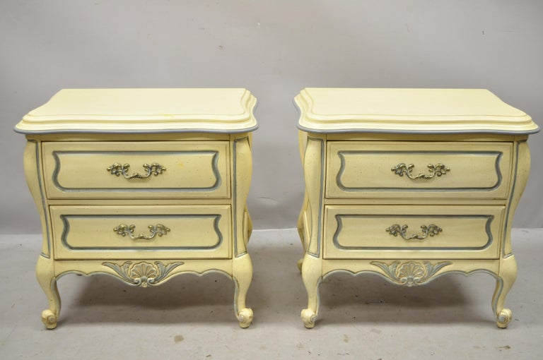 French Provincial Louis XV country style cream lacquer bombe nightstands tables, a pair. Item features cream painted finish with blue trim, shell carved accents, 2 dovetailed drawers, cabriole legs, solid brass hardware, very nice vintage item,