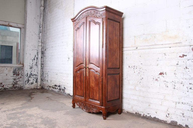 A gorgeous French Country Louis XV style oak wardrobe or armoire dresser  By Hickory Manufacturing Co.  USA, 1970s  Oak and brass  Measures: 38.38