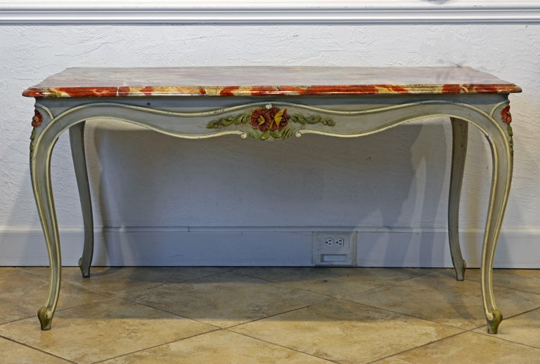 This vintage French Provincial painted dining table in the Louis XV style features a boldly marbleized top above curved aprons centering decorative multi color carved flowers and leaf work on all four sides. The curved aprons continue graciously to