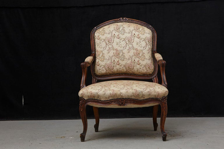 Lovely French Provincial Louis XV style walnut fauteuil, covered in nailhead trimmed fabric, with confirming armrests. The arms with voluted supports, carved apron, the whole raised on cabriole legs, circa 1930s Some minor stains on the seat,