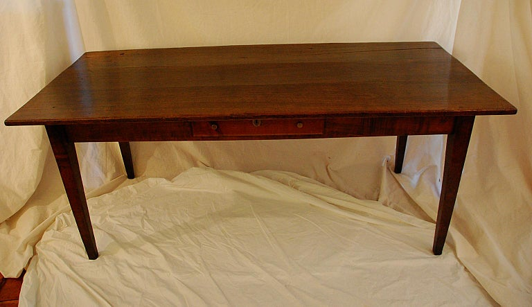 French provincial mid-19th century wild cherry farmhouse table with tapered legs, one side drawer, three board top. This six foot table easily seats eight and has the requisite 24 inch knee room all around; the 32 1/2 inch width makes for