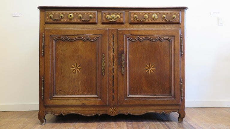 19th century French Provincial sideboard. French credenza walnut and oak with fruit wood inlay, and brass hardware. Excellent Marquetry inlay work throughout the piece. Another detail of hand made craftsmanship notice the angle of the inside panel