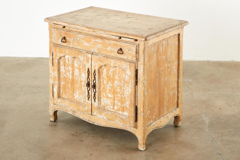 Intentionally aged French provincial style nightstand cabinet. Featuring a pull-out tray or writing table. Beautifully crafted with a pickled lacquer finish having paint remnants to mimic age. Fronted by a large storage drawer and two doors below