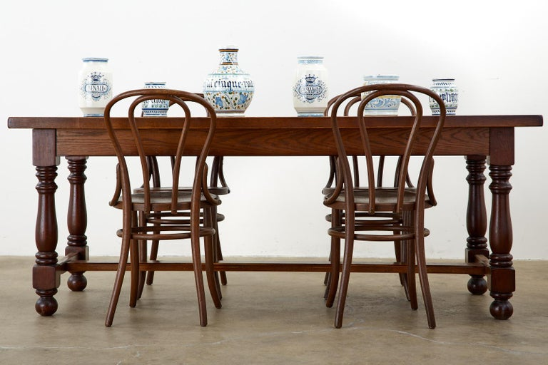 Handsome French farmhouse dining table made in the provincial style crafted from oak. Features a nearly 2-inch thick plank top supported by a trestle style base. The table is constructed with wood peg joinery and has a rich, dark finish. There is