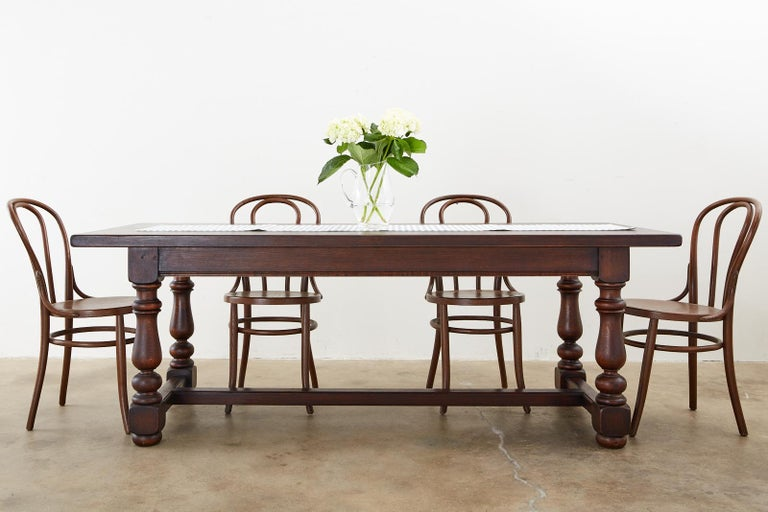 Distinctive French farmhouse trestle dining table made in the provincial style handcrafted from oak. The table features a nearly 2 inch thick plank top supported by a substantial trestle style base. The base has thick, chunky turned legs ending with