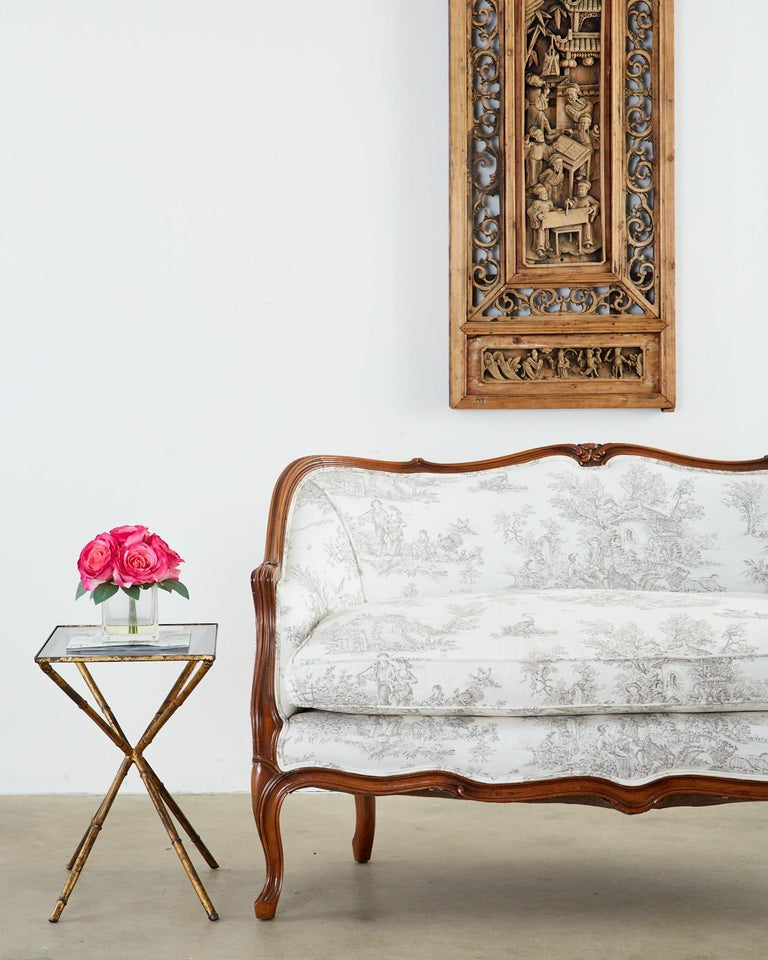 Exquisite French canapé or settee made in the Provincial or Louis XV style. Features a carved walnut frame with a serpentine crest rail and apron. The molded arms gracefully curve down to the seat which is topped with a loose seat cushion.